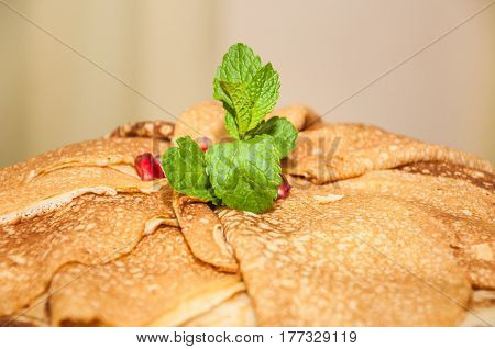 Pancakes decorated with fragrant mint leaves during the celebration Russian Shrovetide