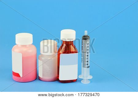 Prescription medicine bottle and oral syringe for baby isolated on blue background