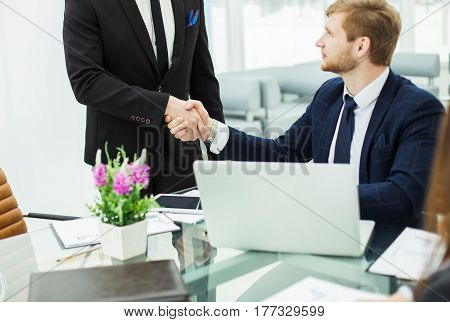 handshake between colleagues in the workplace in a modern office.the photo has a empty space for your text