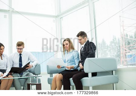 employees of the company with documents sitting in the reception room before the conference.the photo has a empty space for your text