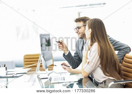 Manager and accountant are sitting and discussing financial charts with profits and expenditures of the company in the workplace in the office.the photo has a empty space for your text