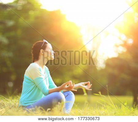 Attractive young woman in lotus position in the park on a sunny day