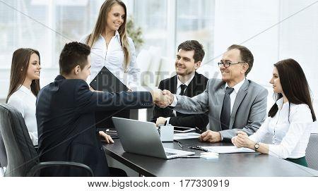 Business meeting at the table and handshake of business partners