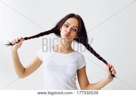 Squint eyed playful beautiful woman showing funny face weird expression isolated on white background. Copy space text.