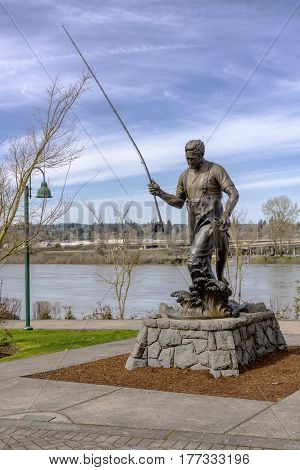 Statue of a fisherman and the Willamette river in Salem Oregon.