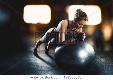 Muscular woman on a fitness ball with sports underwear at the gym