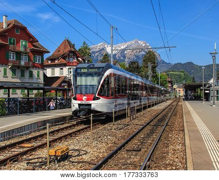 Stans, Switzerland - 8 May, 2016: the Stans railway station with a passenger train heading to the city of Lucerne at its platform, Mt. Pilatus in the background. The town of Stans is the capital of the Swiss canton of Nidwalden.