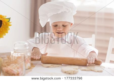 A small child in the form of a cook rolls out the dough on the kitchen table