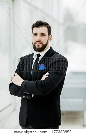 portrait of successful businessman standing near a window in bright office.the photo has a empty space for your text