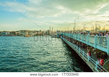 ISTANBUL, TURKEY - SEPTEMBER 28: Looking towards the New Mosque, Yeni Cami, from the Galata Bridge with lot of fishermans fishing with rods on September 28th, 2013 Istanbul, Turkey.