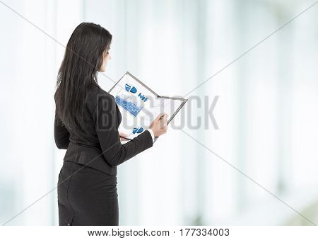 A young, attractive, successful business woman examines graphics at the office
