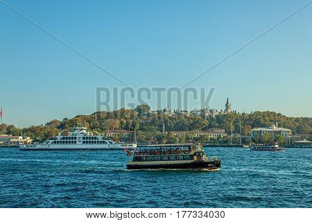 ISTANBUL, TURKEY - SEPTEMBER 29: Ships returning to the Istanbul seaport after sailing Bosphorus with a view to the Topkapi palace on September 29th, 2013 Istanbul, Turkey.