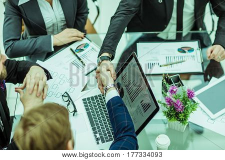 handshake of business partners on the background of financial graphs lying in the workplace