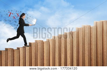 Happy asian business woman walking up staircase with taxes text from laptop screen