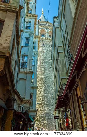 ISTANBUL, TURKEY - SEPTEMBER 28: View of the famous medieval landmark Galata Tower in the old narrow street in the city center on September 28th, 2013 Istanbul, Turkey.