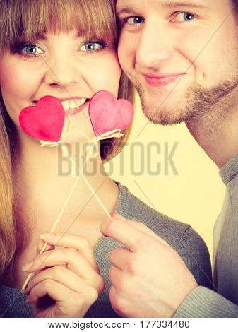 Love symbol romance relationship fun leisure concept. Girl with boy playing together. Youthful couple holding hearts smiling.