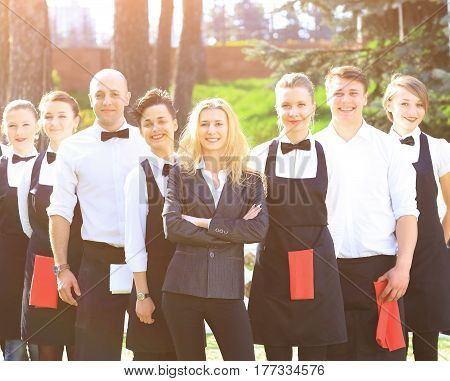 A large group of friendly waiters and waitresses standing row behind each other