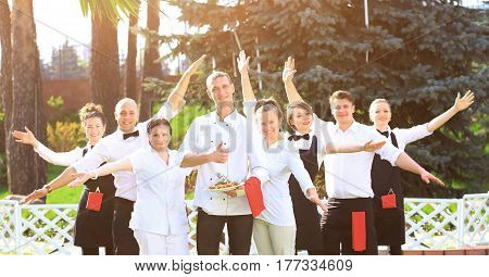 A large group of happy and emotional waiters standing in a row behind each other are happy to raise their hands up