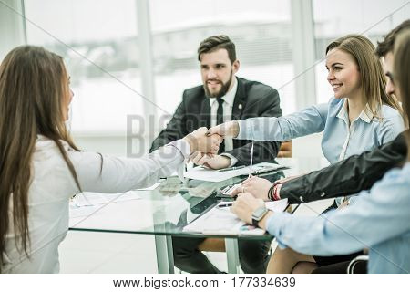 handshake business partners after discussing the terms of a new contract in the workplace in a modern office.the photo has a empty space for your text