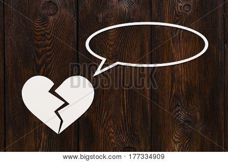 Paper broken heart is talking or thinking on wooden background. Abstract conceptual image with copyspace