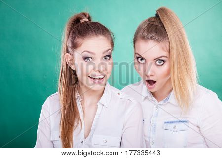 Two young women looking shocked surprised stunned. Human emotion face expression