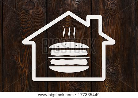 Paper house with burger inside on wooden background fastfood concept. Abstract food conceptual image