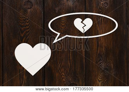 Paper heart is thinking about broken one on wooden background. Abstract conceptual image
