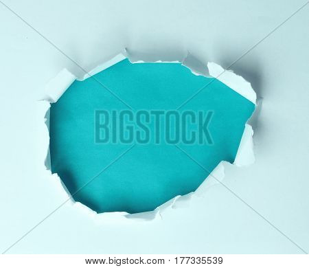 A torn hole in the paper on a blue background for your advertising text