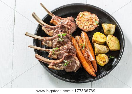 Tasty Grilled Ribs Of Lamb With Vegetables On White Table
