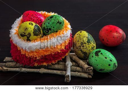 Colorful painted easter eggs in yarn socks on black background