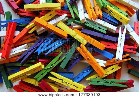 The multicolored clothespins on the white background. The colorful background.
