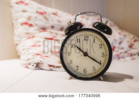 Retro alarm clock with 10 O'clock and twenty minuet, on white bed with pillow