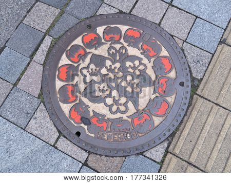 Nagano, Japan - February 22, 2017 - Manhole cover of Nagano engraved with apple. Apples are one of the special products of Nagano. The yield of apples in Nagano is the second largest in Japan.