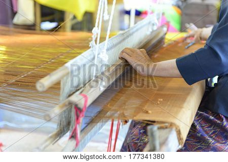 Close up of gold silk weaving on loom cotton on the manual wood loom in Asian traditional culture and woman hand weave lifestyle