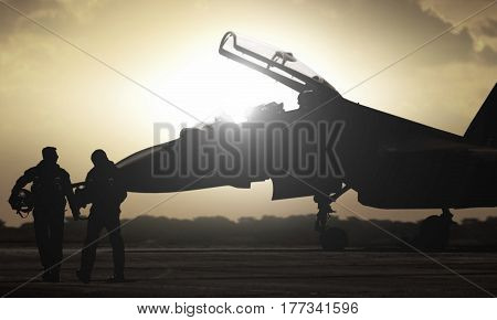 Military aircraft pilot walking during sunset with sun glare
