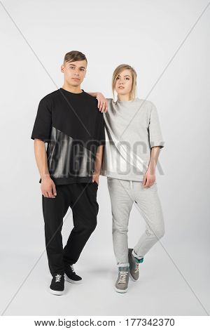 Boy and girl. Young muscular man wearing black clothes and sneakers with girl in grey clothes isolated on white background