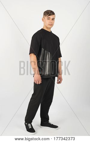 Young muscular man wearing black clothes and sneakers isolated on white background