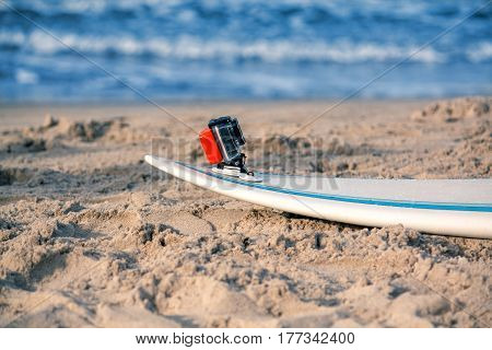 Surfboard with attached action camera lies on the sand on the beach. Action camera is in waterproof case for swimming. Ocean on background
