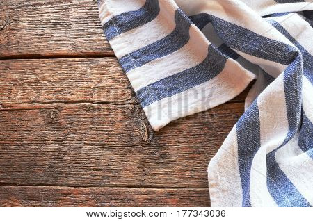 A top view image of a dish towel on an old wooden kitchen table top.