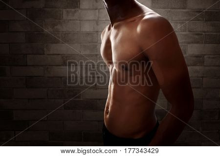 Muscular man body with brick wall background