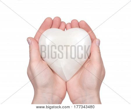 Young woman holding polished cream white carved onyx heart on white background