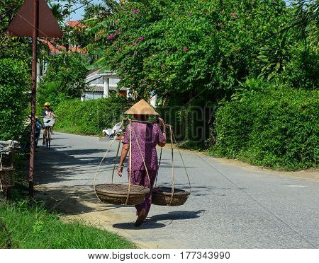 Vendor Walking On Rural Street In Vietnam