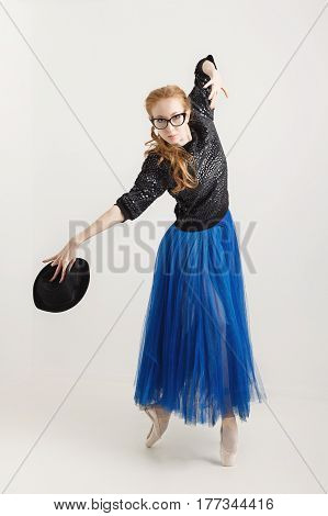 Sweet hipster ballerina in a tutu pointe shoes and sunglasses dancing with a hat. Modern dance. Youth culture