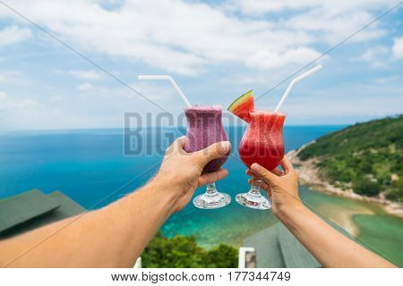 Fruit shake from fresh watermelon and blueberries on the outstretched hand of a man and a woman against a background of a tropical landscape. Luxurious vacation.