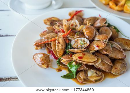 Close focus on cooked clams with chili paste sauce and basil leaf on white dish. Tastes are spicy and salty.