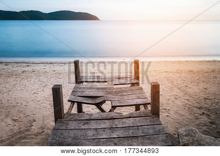 Old broken wood terrace on yellow sand beach. Water in blue with smooth and flat surface. Warm sunlight from summer sky before sunset.