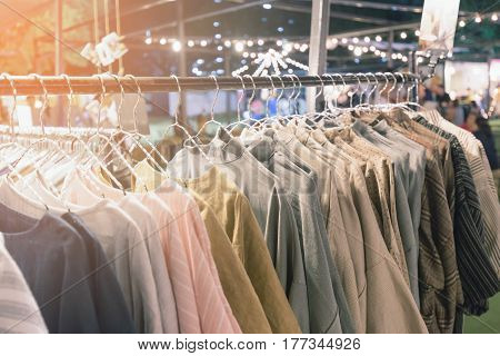 Close focus on hand made cotton woman shirts in difference design hanging on clothes bar in retail shop of outfit market.