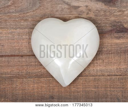 Polished cream white carved onyx heart on wooden vintage tray background