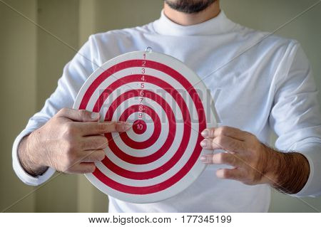 young man holding a dartboard finger point the target