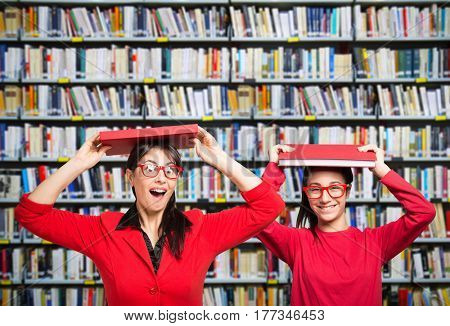 Smiling woman and teenager in a library